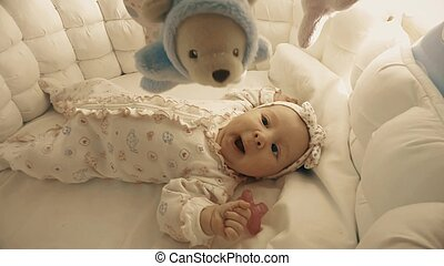 Newborn baby girl about to sleep in her cot