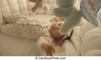 Newborn baby girl about to sleep in her cot - Newborn baby...