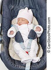 newborn baby girl in a car seat