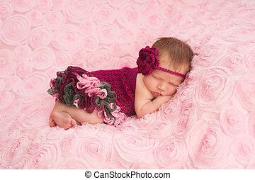 A sleeping newborn baby girl wearing a maroon crocheted headband and romper. She is sleeping on her stomach on pink rose ribbon fabric.