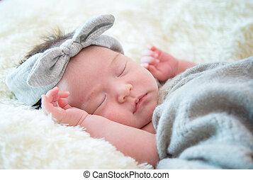 Newborn baby girl is sleeping on fur blanket