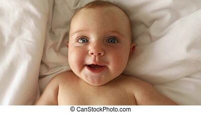 Newborn baby girl laughs lying on her back on the bed