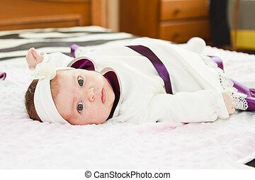 Newborn baby girl looking at camera
