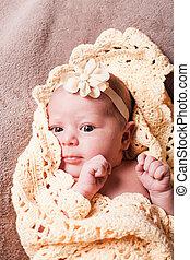 Newborn baby girl on the crochet blanket