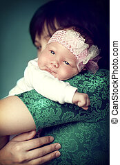 Newborn baby girl on the shoulder mom