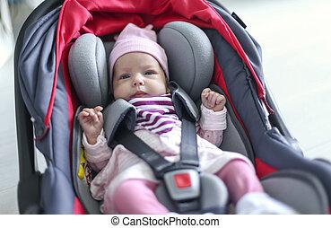 Newborn baby girl sitting in a car seat
