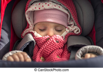 Newborn baby girl sitting in a car seat