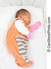 Newborn baby girl sleeping in her bed