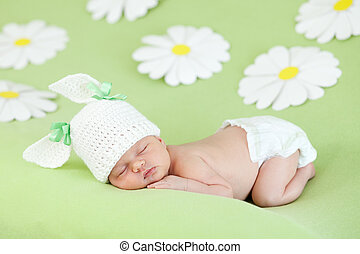 newborn baby girl sleeping on green meadow among daisy