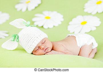 newborn baby girl sleeping on green meadow among flowers