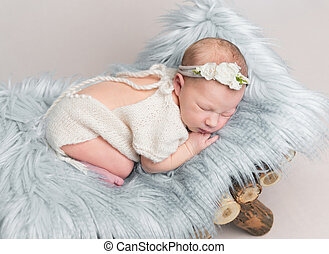 Newborn baby girl sleeps on small wooden crib.