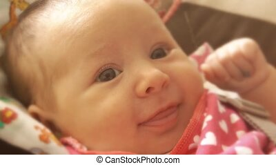 Newborn baby girl smiles