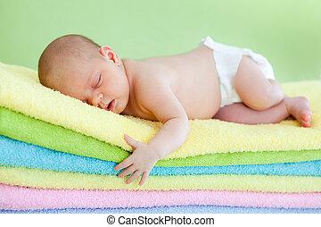 newborn baby girl weared cap sleeping on colourful towels -...