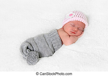 Newborn baby girl wearing a pink hat.