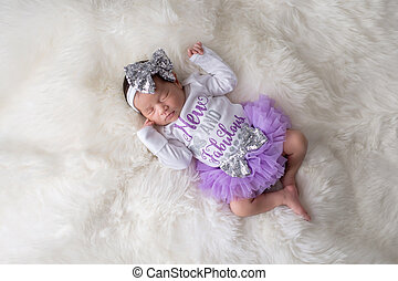 """Portrait of a 12 day old newborn baby girl wearing frilly, purple, tutu bloomers and a white onesie that say, """"New and Fabulous"""". Shot in the studio on a white sheepskin rug."""