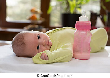 Newborn baby girl with a bottle of milk The concept of food and parenting