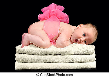 Newborn baby girl with a pink bow