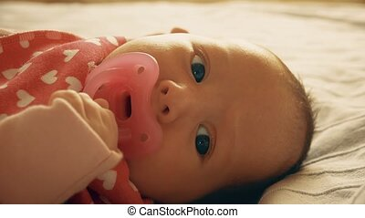 Newborn baby girl with pink pacifier