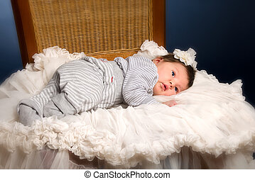 Newborn baby girl with sleeping on a wooden chair