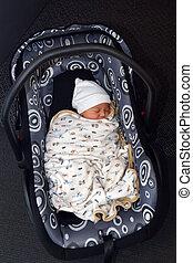 Newborn baby in a car seat