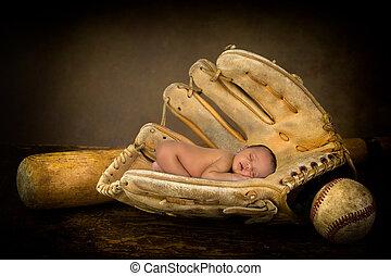 Newborn baby in baseball glove