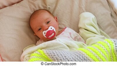 Newborn Baby in Crib Looking Up at Mobile Overhead