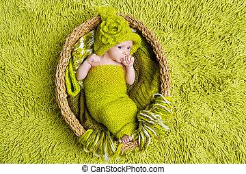 Newborn baby in woolen hat inside basket over green background