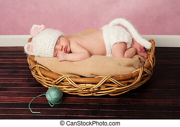 13 day old newborn baby girl wearing a white, crocheted kitten costume and sleeping on her tummy in a basket.