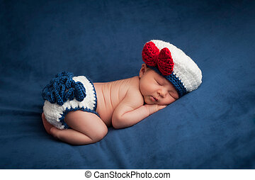 Eight day old newborn baby girl wearing a white and blue sailor costume. She is sleeping contentedly on her stomach. Shot in the studio on navy blue velvet.