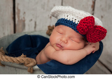 Eight day old newborn baby girl wearing a white and blue sailor hat with red bow. She is sleeping inside of a galvanized bucket with burlap handles. Shot in the studio on a rustic whitewashed wood backdrop.