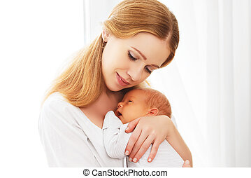 newborn baby in tender embrace of mother