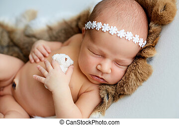 Newborn baby in the hat sleeping with a toy