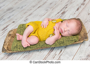 newborn baby in yellow costume sleeping on wooden cot