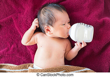 Newborn baby infant eating milk from bottle.