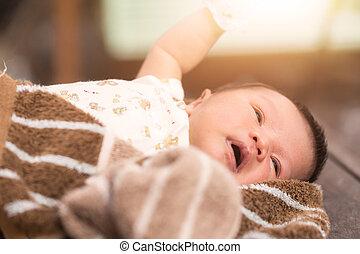 Newborn baby lying on fur fabric.