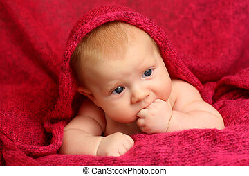 Newborn baby on red blanket
