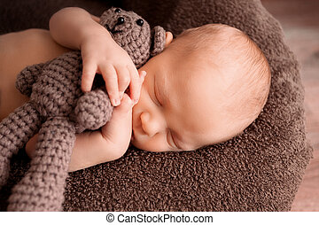 Newborn baby sleeping in a beautiful pose with a little bear