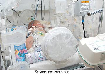 newborn baby sleeping in an incubator in hospital