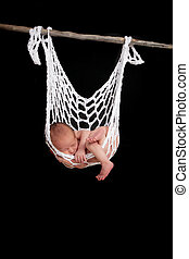 baby sleeping in string hammock