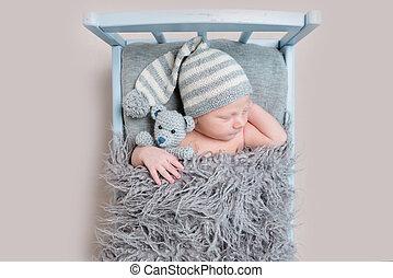 newborn baby sleeping on a bed