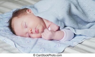 Newborn baby sleeping on a bed covered with a blue blanket