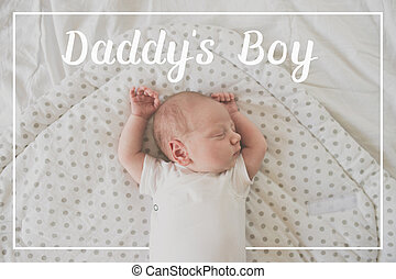 Newborn baby sleeping on bed. Fathers day.