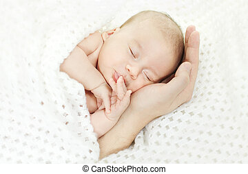 Newborn baby sleeping on parent hand. Concept: kid protection by parents. Closeup.