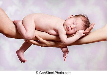 Newborn baby sleeping on parents hands
