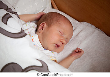 Newborn baby sleeping on the bed, selective focus