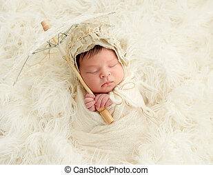 newborn baby sleeping with decorative umbrella