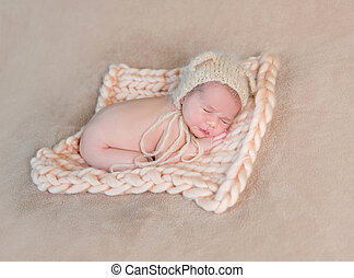Newborn baby sleeps on his tummy.