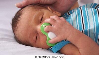 Newborn baby sucking a pacifier. Close-up.