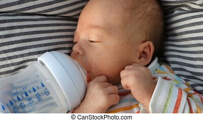 Newborn baby sucks pacifier, bottle with water
