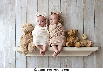Twin baby sisters wearing crocheted bear bonnets and sitting on a wooden shelf alongside three stuffed bears.